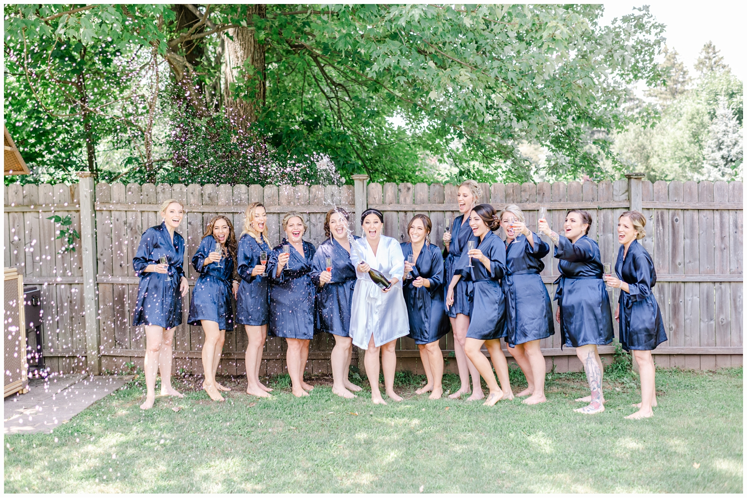 bride and bridesmaids in blue silk robes opening a bottle of champagne