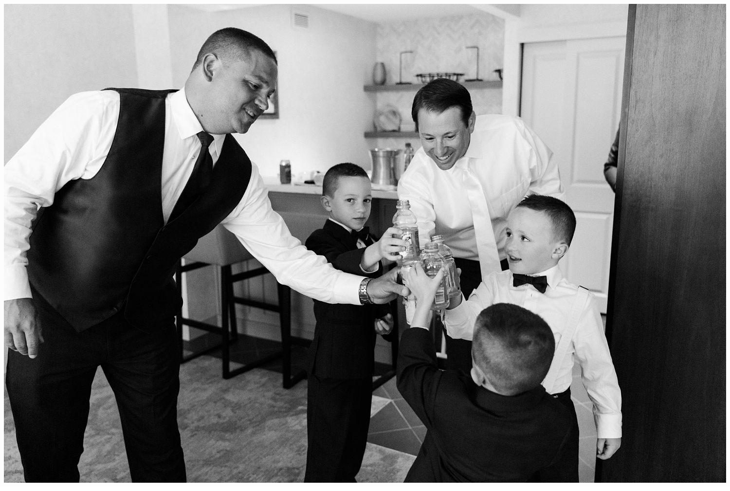 groom and ringbearers toasting on wedding day