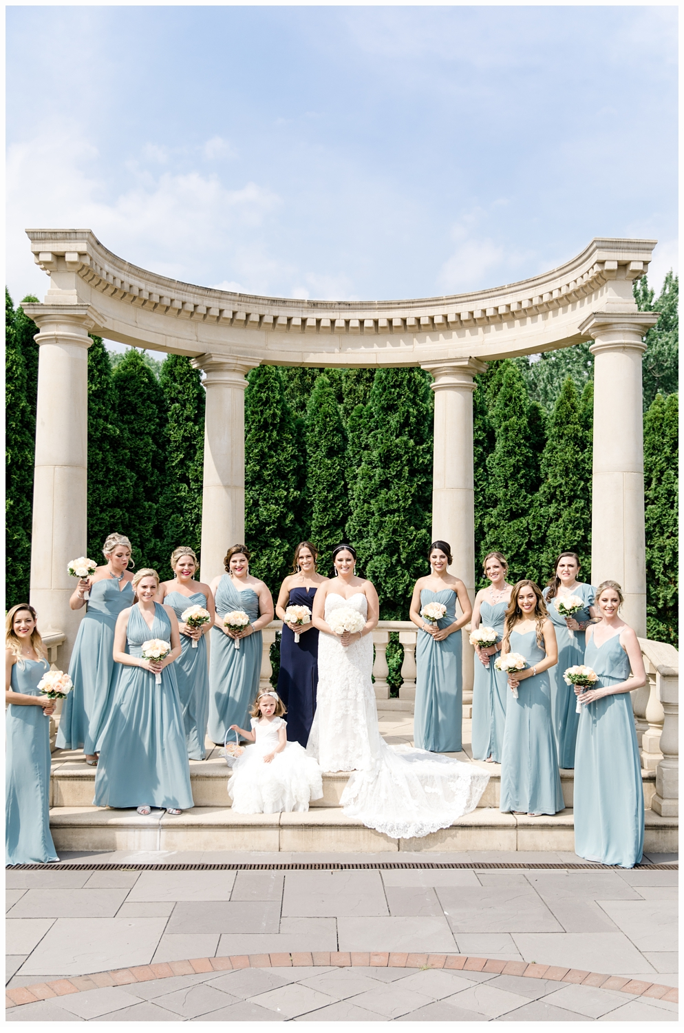 bride and groom with bridesmaids and flower girl posing for a photo