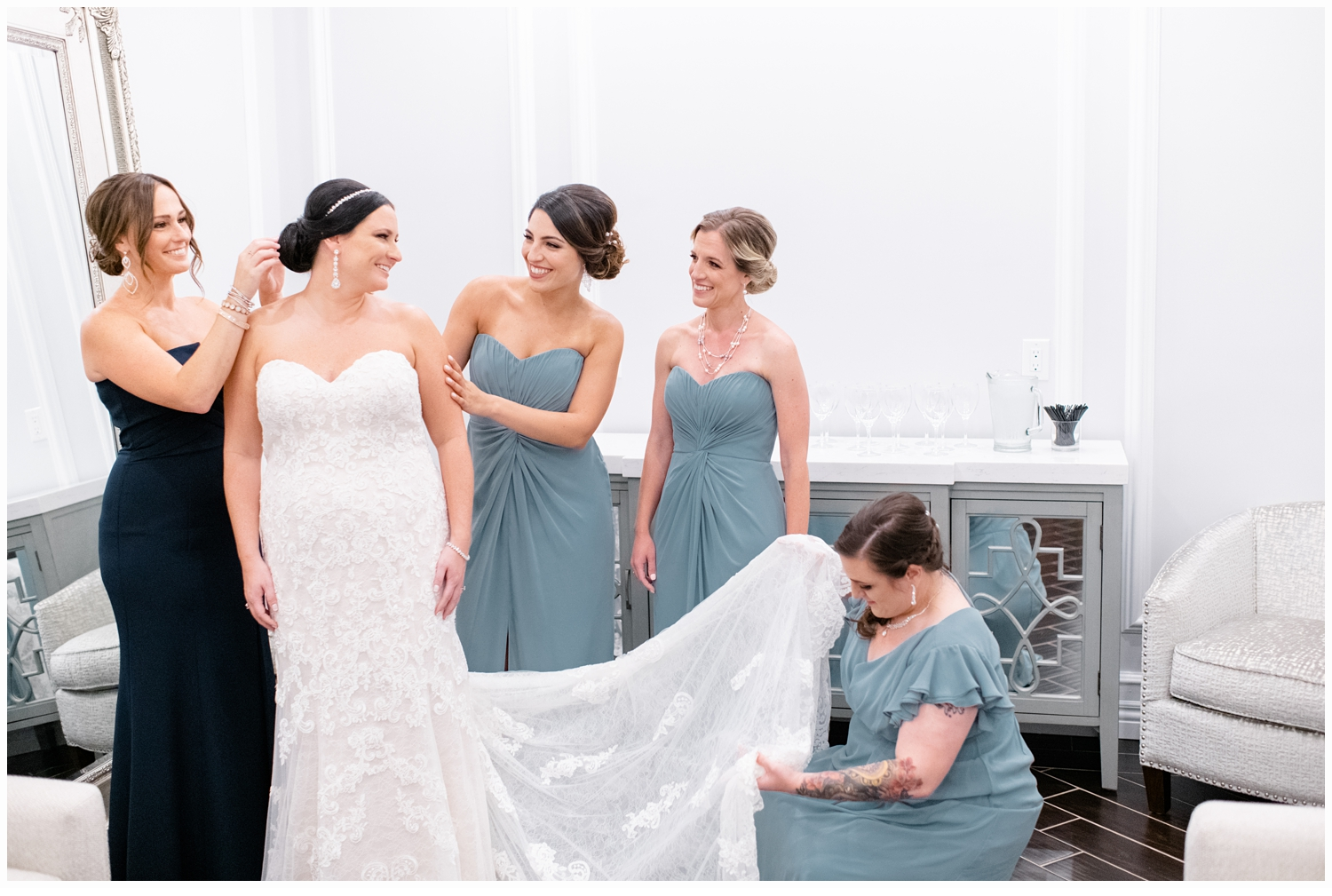 bridesmaids helping bride on with her wedding gown