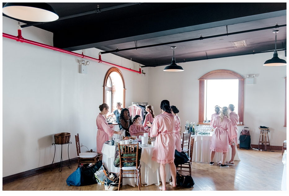 bride and bridesmaids in bridal suite wearing pink silk robes
