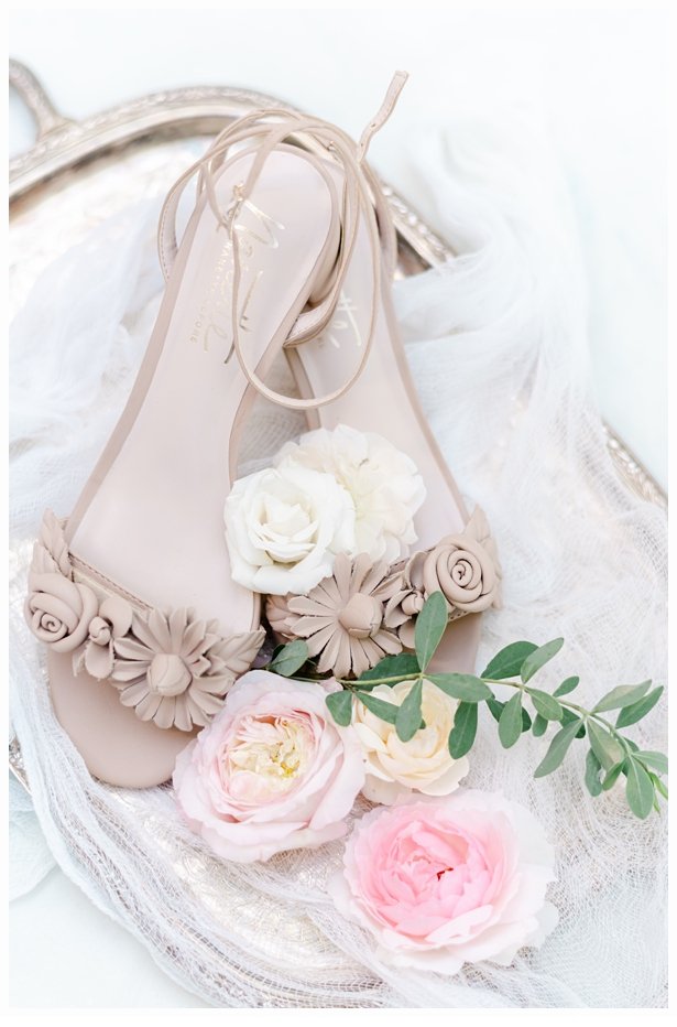 beige wedding shoes on a gold tray