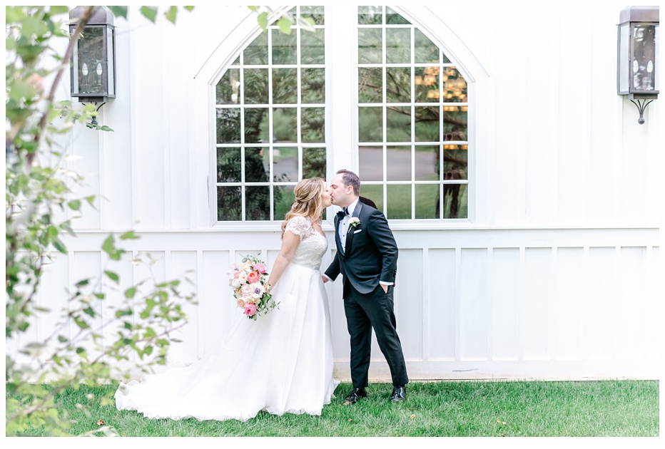bride and groom kissing in front of a pretty white window
