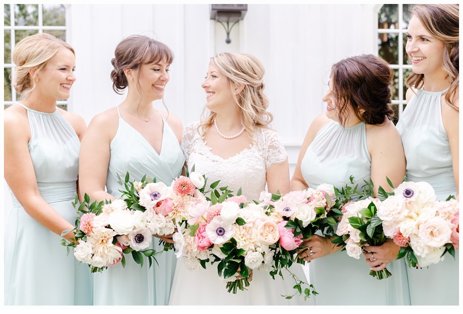 bride and bridesmaids laughing holding bouquets
