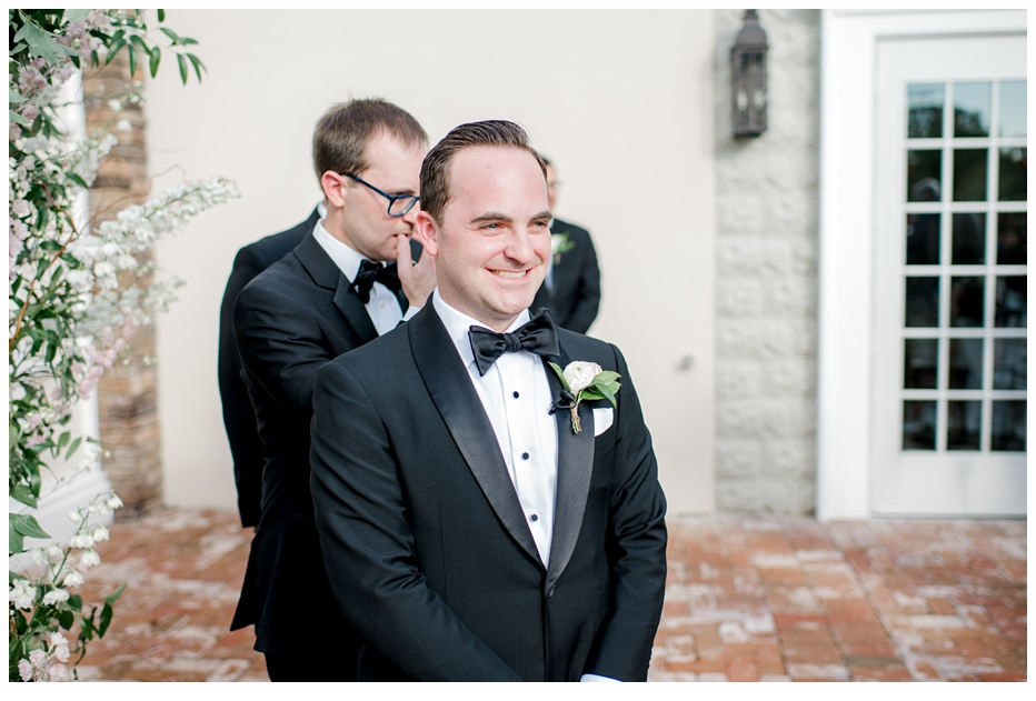 groom smiling as he sees his bride