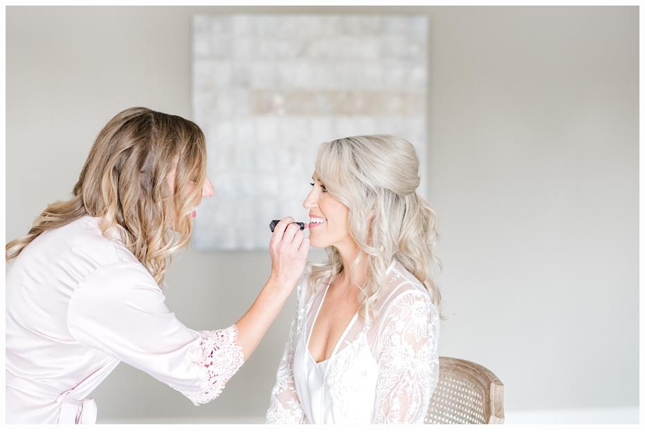 maid of honor applying lipstick on bride