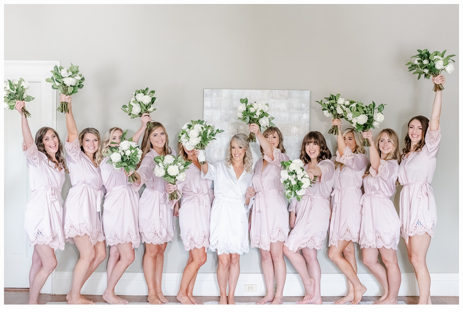 bride and bridesmaids cheering with their bouquets