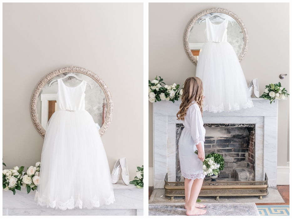 flower girl looking up at her dress hanging on a mirror