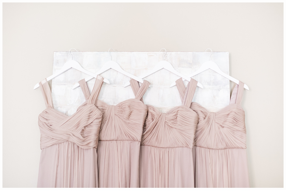 bridesmaids taupe colored dresses hanging up on a picture