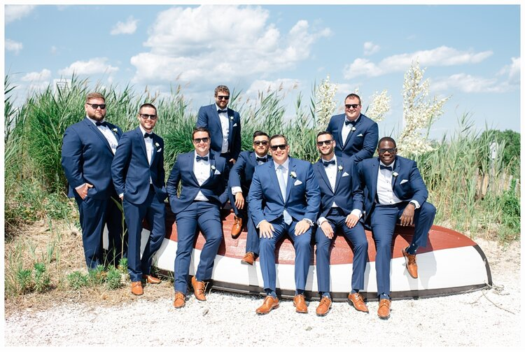 groom and groomsmen sitting on a boat