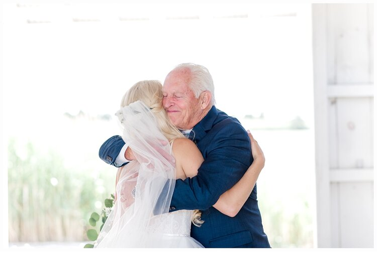 bride and dad hugging on wedding day
