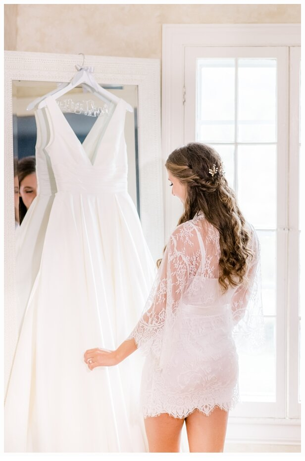 bride wearing a white robe looking at her wedding dress in mirror
