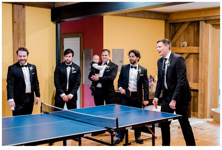 groom and groomsmen playing ping pong