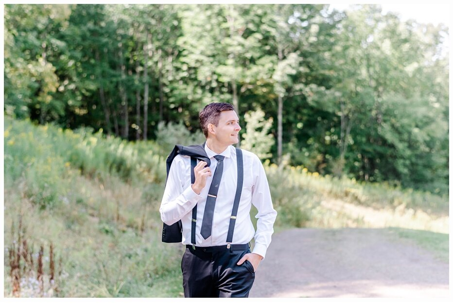 groom carrying his suit jacket over his shoulder