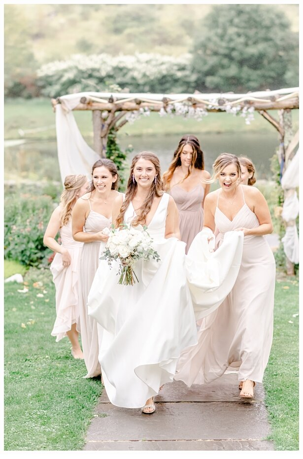 bridesmaids carrying the train of a brides gown