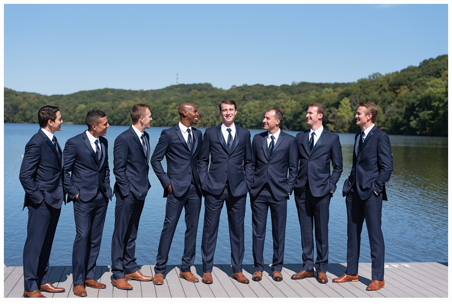 groom and groomsmen on a dock on a lake