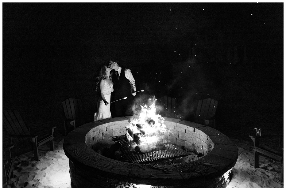 bride and groom roasting marshmellow's by the fire on a beach