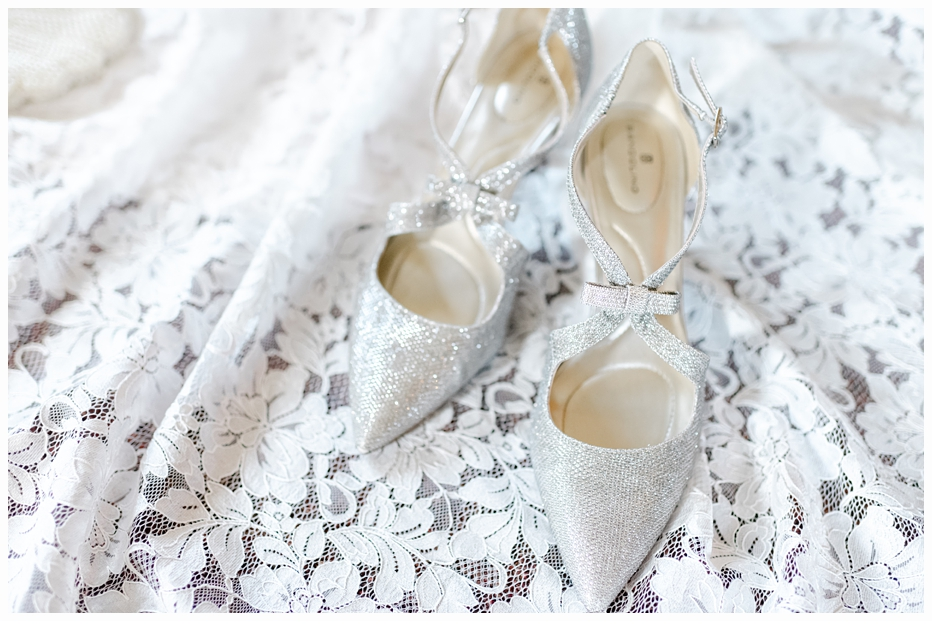 silver bridal shoes on the wedding gown