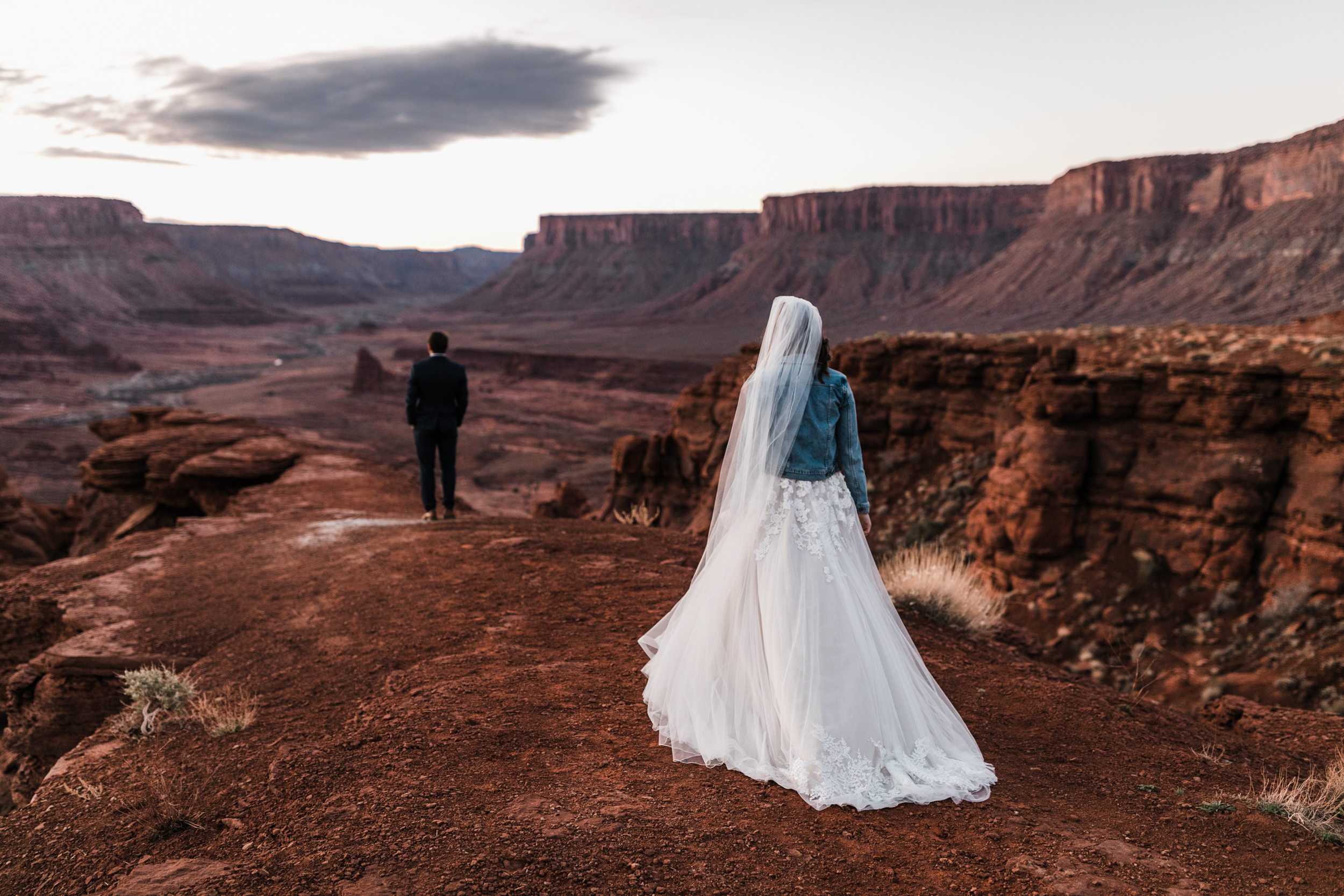 Bride walking up for first look with views over moab desert.