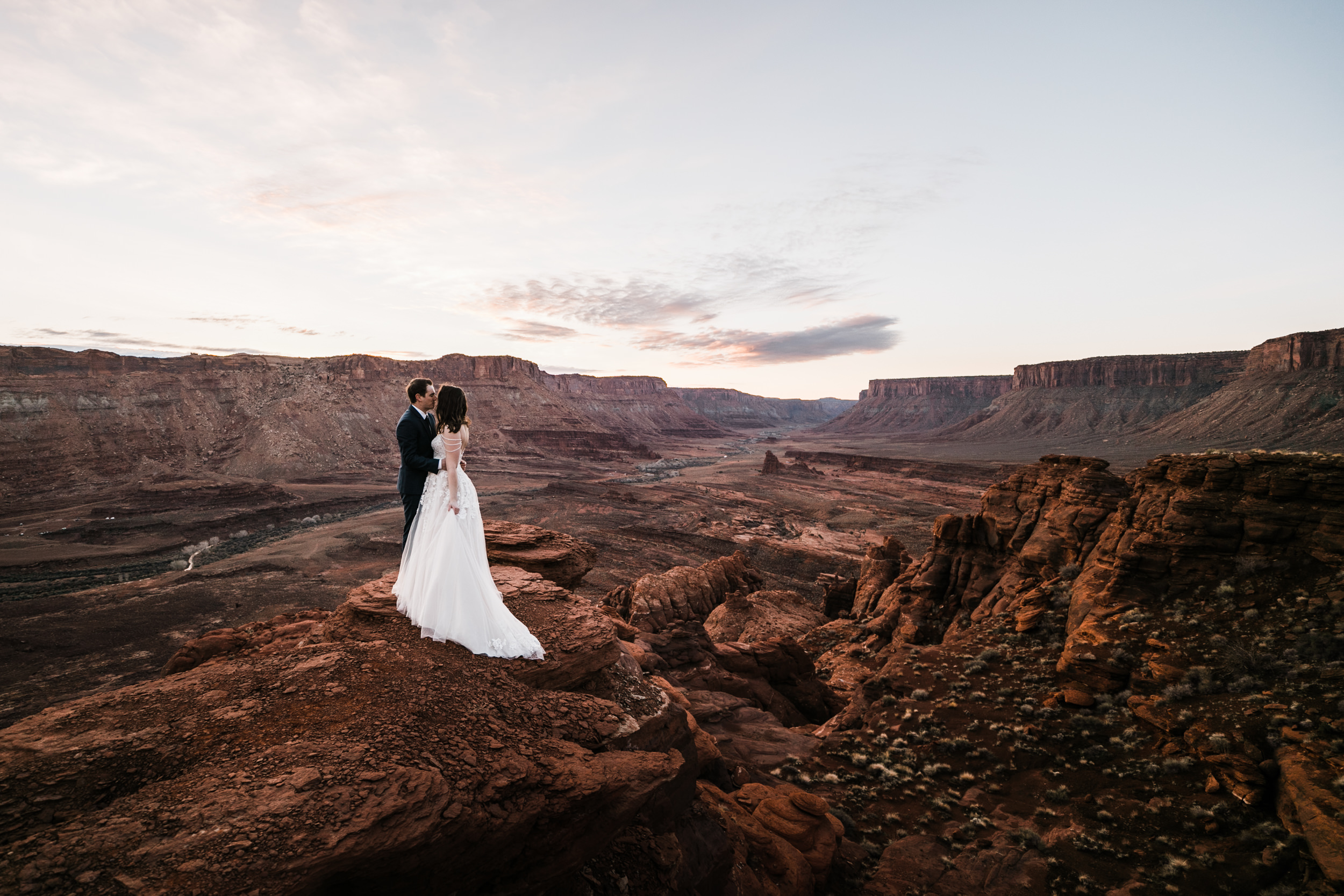 The views in the desert make for amazing wedding photos. Moab, Utah sunrise before their wedding in arches national park.