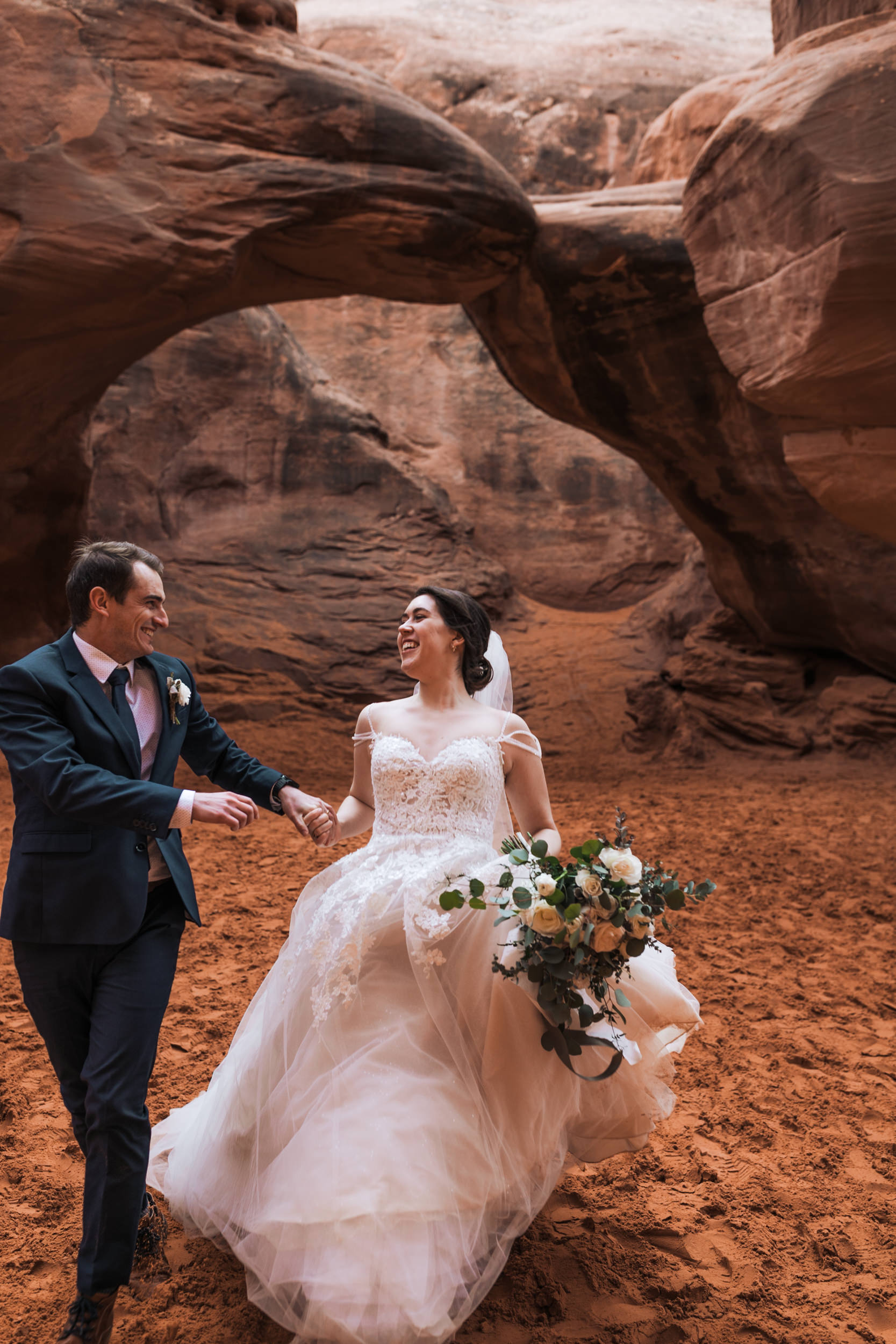 His suit was so cool and her wedding dress was absolutely stunning. Such a handsome couple hiking in Arches National Park together.