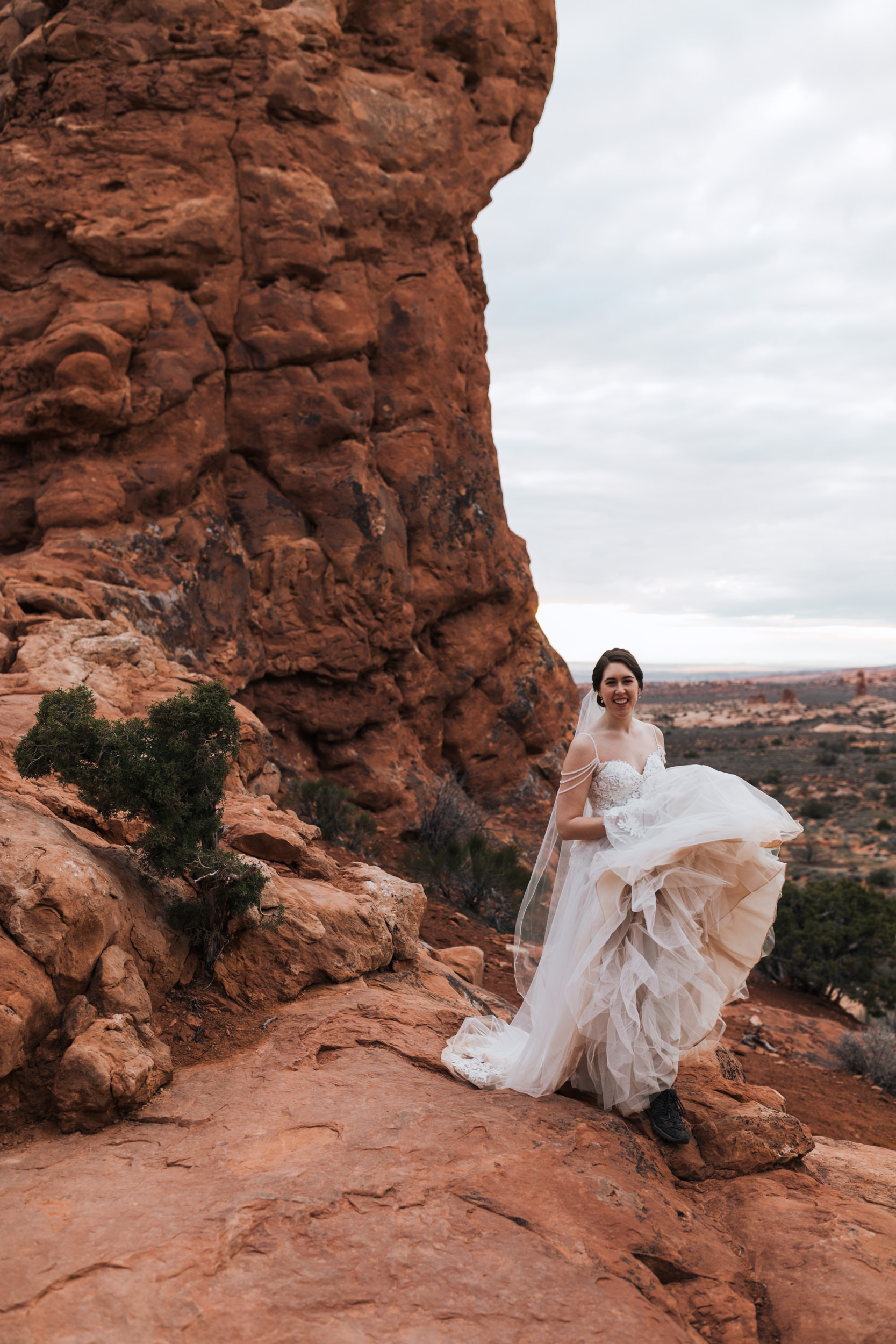 Claire loved hiking around Arches and here, shows how a bride rocks boots with a dress in the desert.