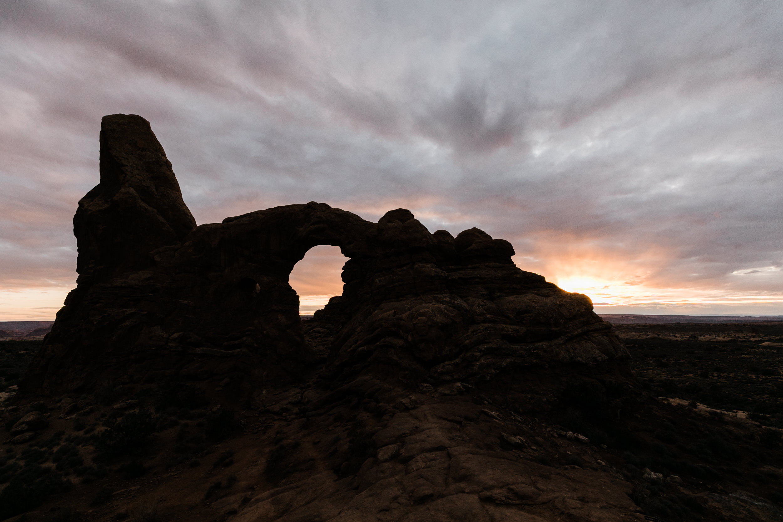 Turret Arch at sunset in Arches National Park. Our wedding couples love to hang out after we're done taking photos just to relax and watch as the sun dips behind the desert horizon in Moab.