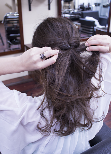 "2) Take the top knot and place your fingers and the middle. Spread the knot by pulling left and right to create a hole. Now lift the pony tail and pull through the hole you just made. We call this a ""kururin-pa"" in Japanese.  3) Tug under the knot left and right to tighten and lift the band."