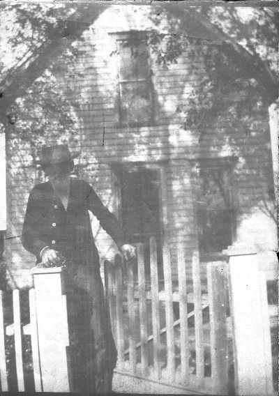 Notation on back:  C. R. Garrett, Harley's father in front of the old home in Macksburg, Iowa