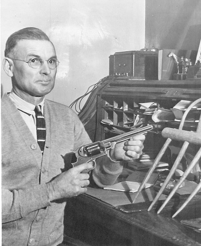 Harley U. Garrett, posing with pistol Undated photo, probably before 1948 Likely taken at his office in St. Charles, Iowa