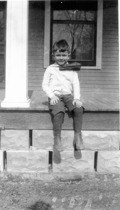 """Wind was blowing his tie. Kenneth was on Grandma Jessup's porch in Macksburg, May 1918. Were there for Grandma Garrett's funeral."" Written by his mother."