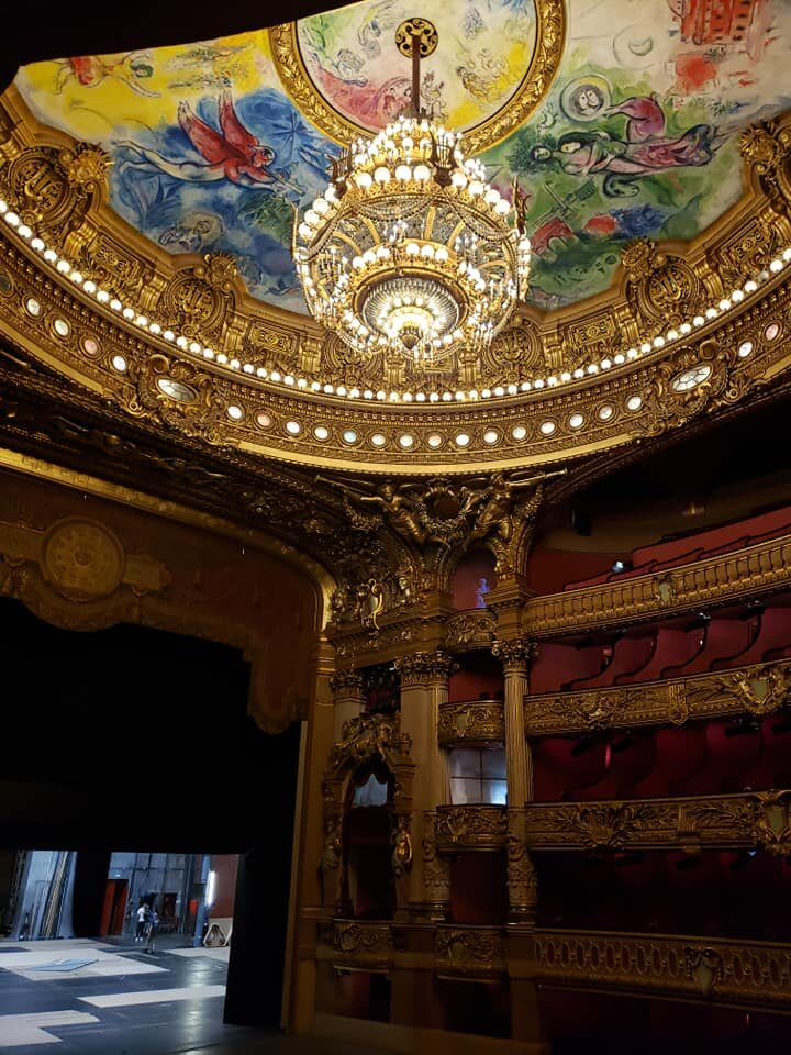 Inside the theater itself. The chandelier weighs 7 tons. The ceiling area which surrounds the chandelier was originally painted by Jules Eugène Lenepveu. In 1964 a new ceiling painted by Marc Chagall was installed on a removable frame over the original. It depicts scenes from operas by 14 composers.