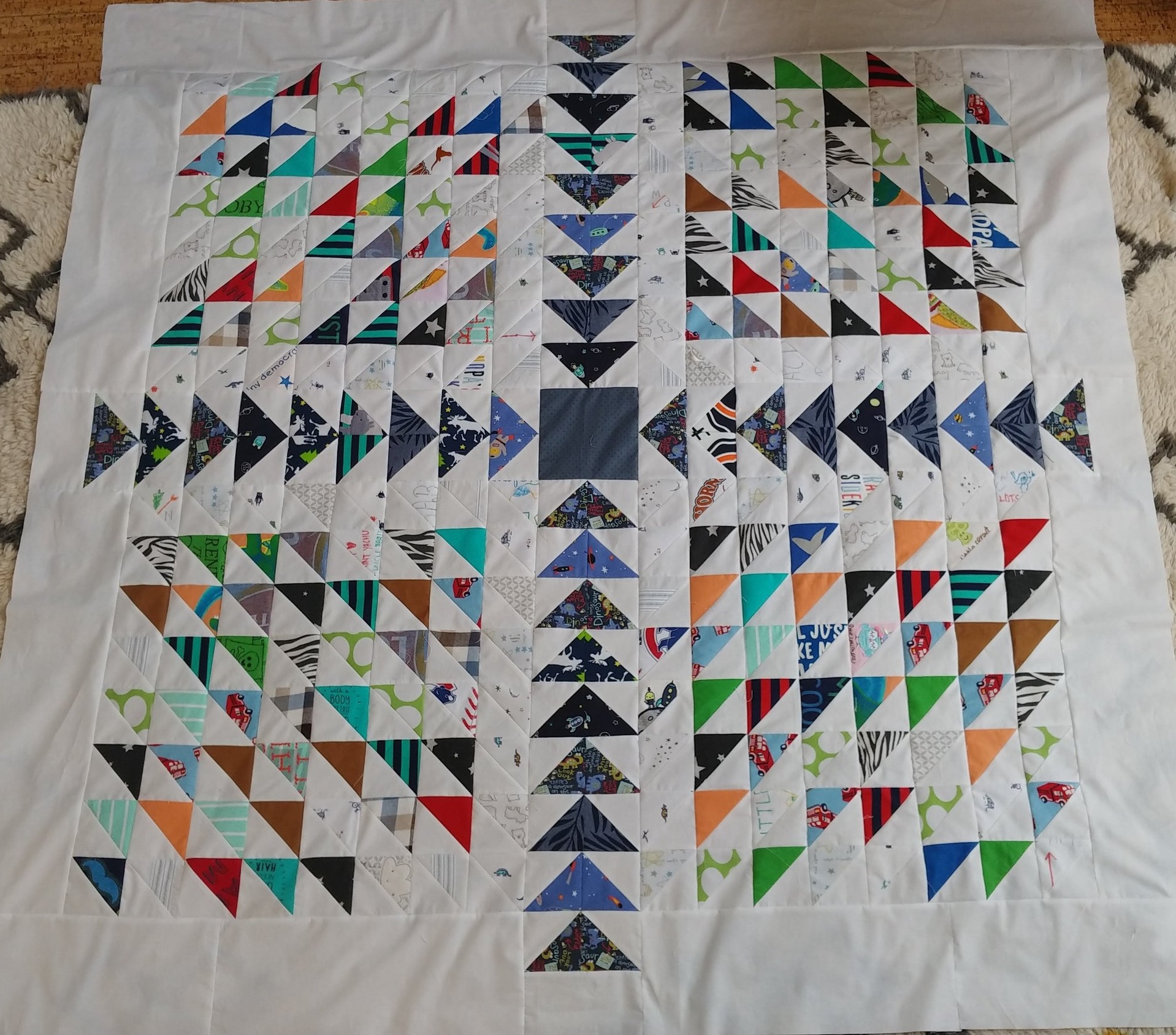 Modern quilt top made with baby clothes.