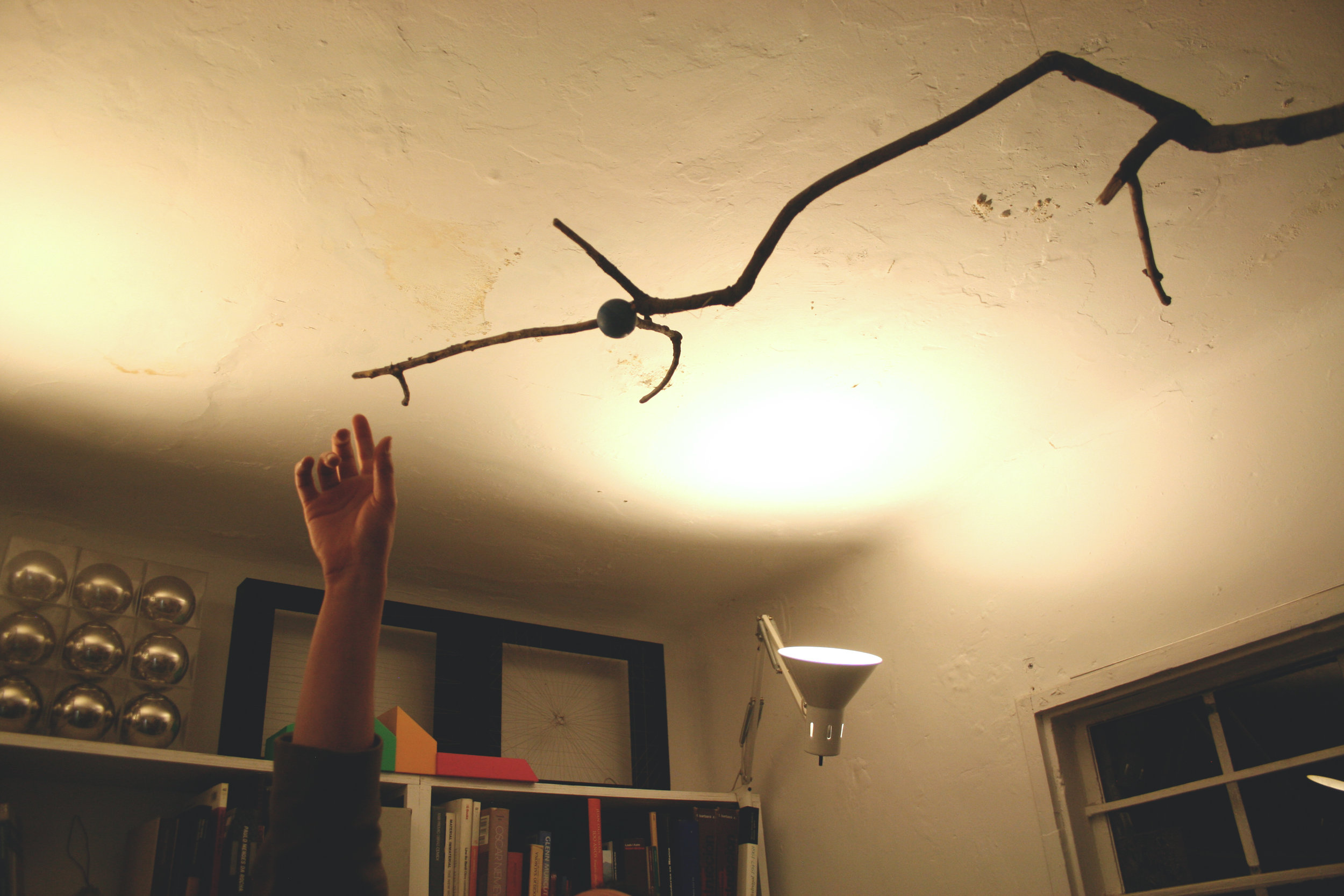This is a hanging mobile made with a tree branch and a foam ball