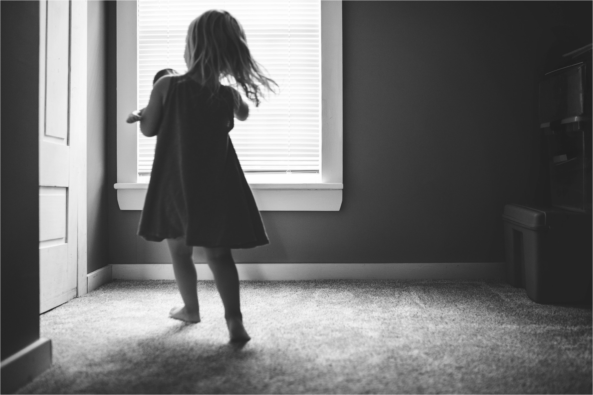 little girl running by the window