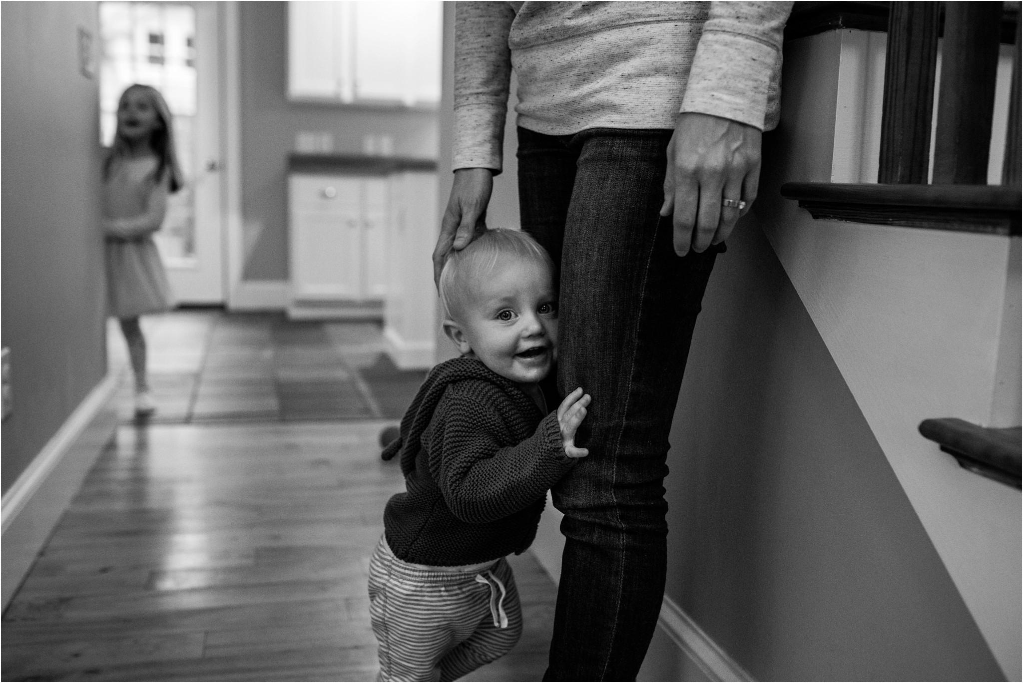 little boy grabbing mom's leg