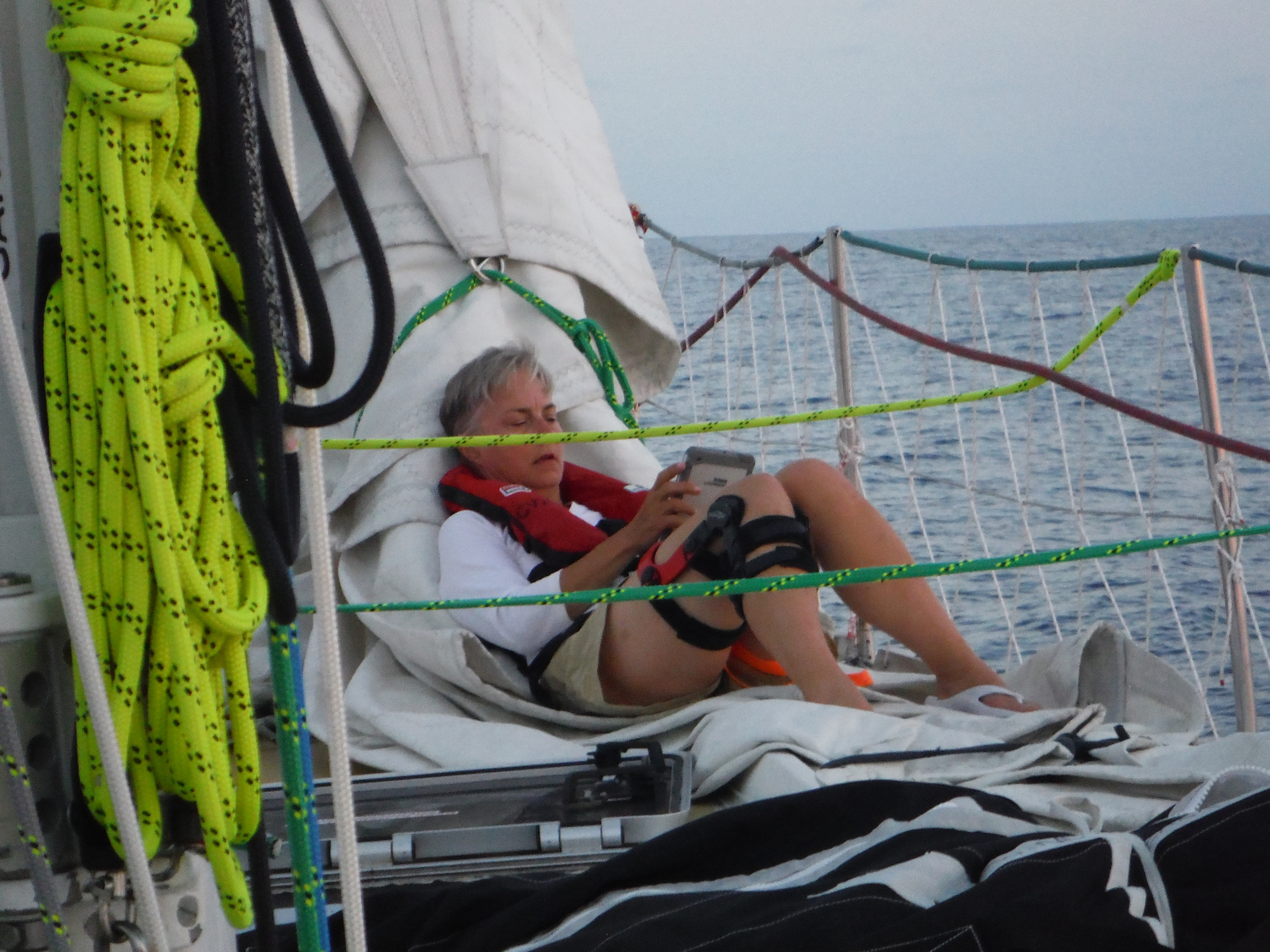 Relaxing on deck while off watch, sitting on the staysail, trying to beat the heat down below. A bit of breeze and cloud cover a welcome relief.