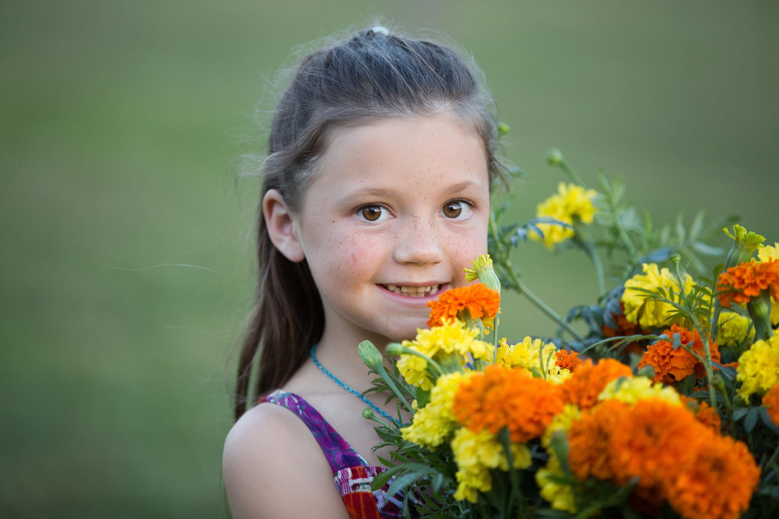 Kid holding organic marigolds grown on a local flower farm