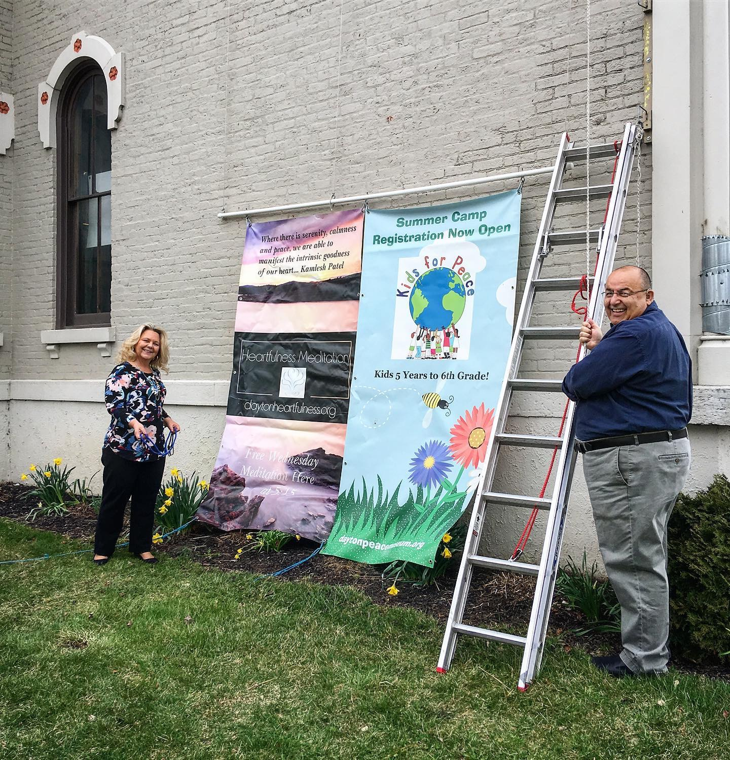 Dayton Convention and Visitor Center  employees Sonja and Iggy get roped into helping hoist banners on the side of the Museum one recent and windy day!