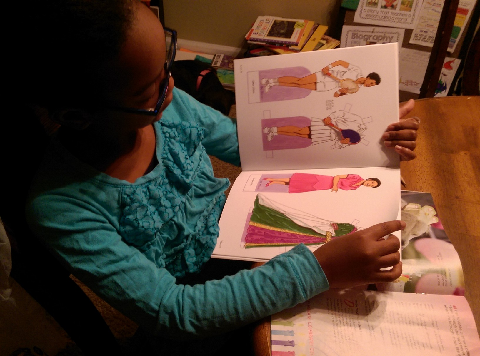 daughter checking out the beautiful African-American women in the paper dolls book