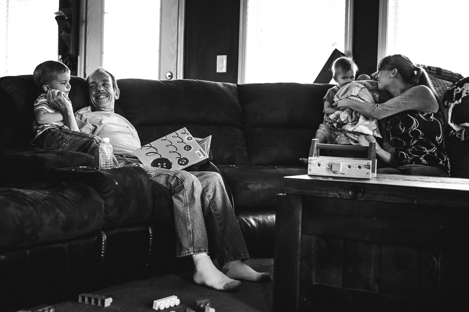 family reading and playing on couch