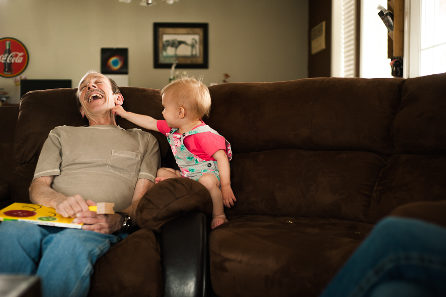 granddaughter tickling grandpa