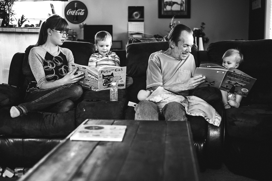family reading book on couch