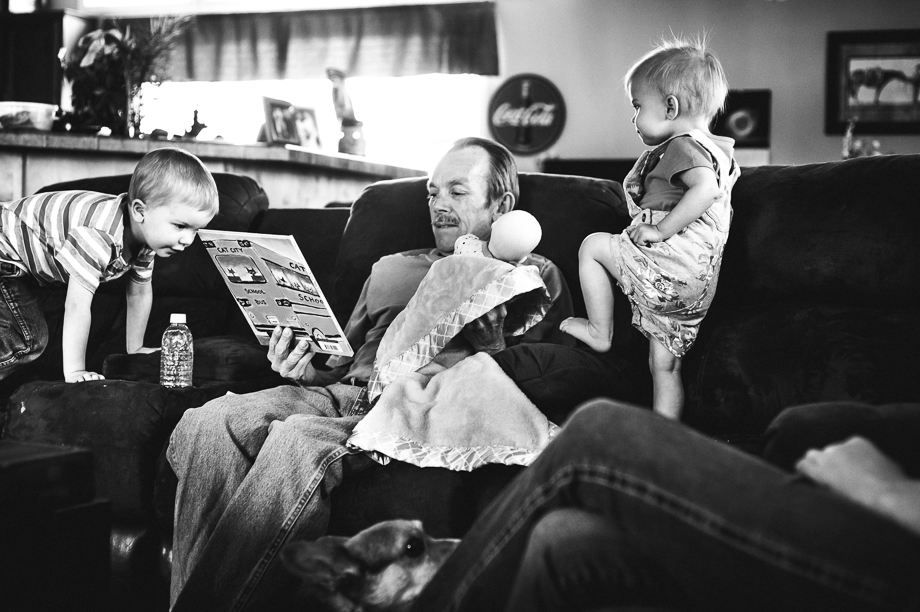 grandpa reading and holing doll while grandkids walk