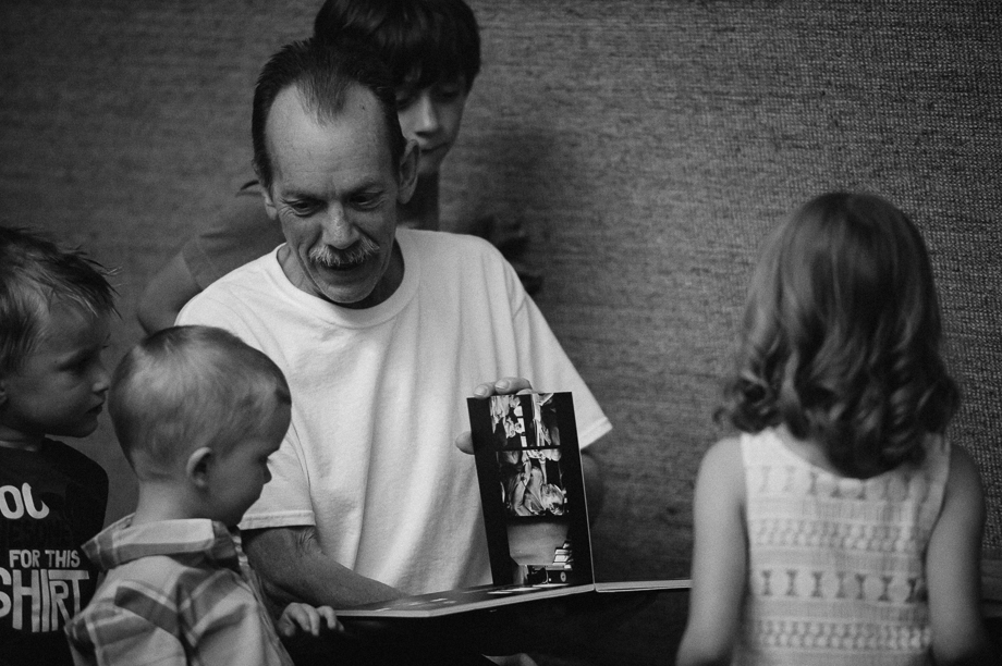 grandpa looking at photo album with grandkids