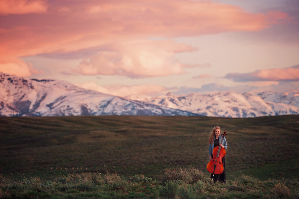 girl at sunset with cello and mountain range
