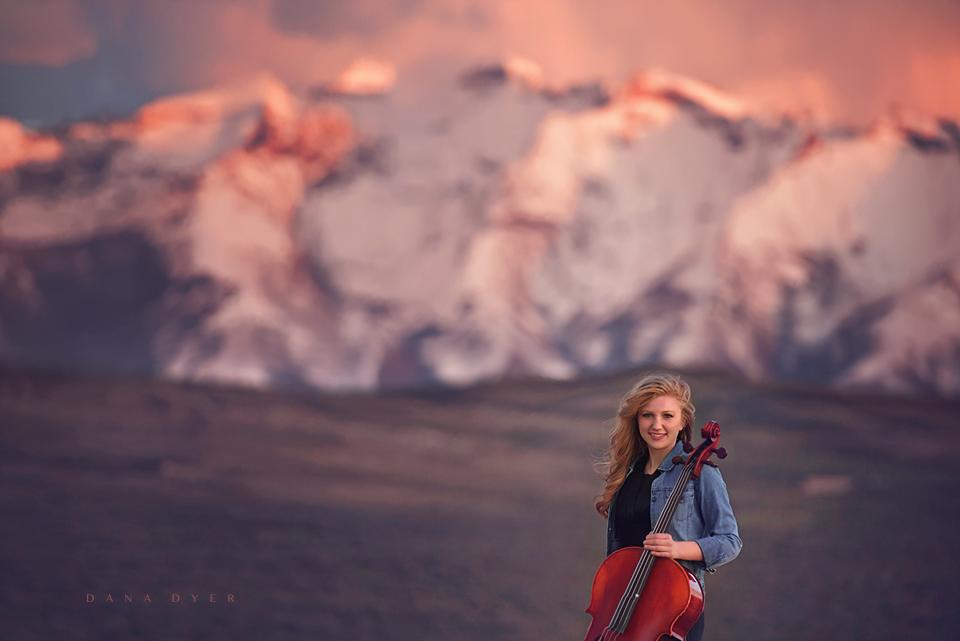 girl on mountain range with cello