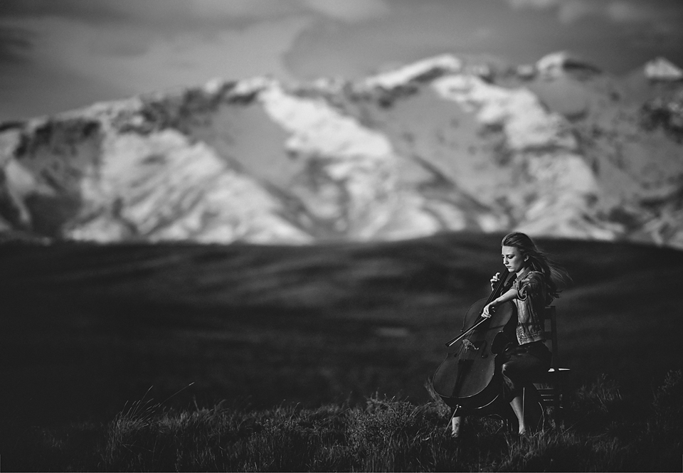 woman playing cello by mountain