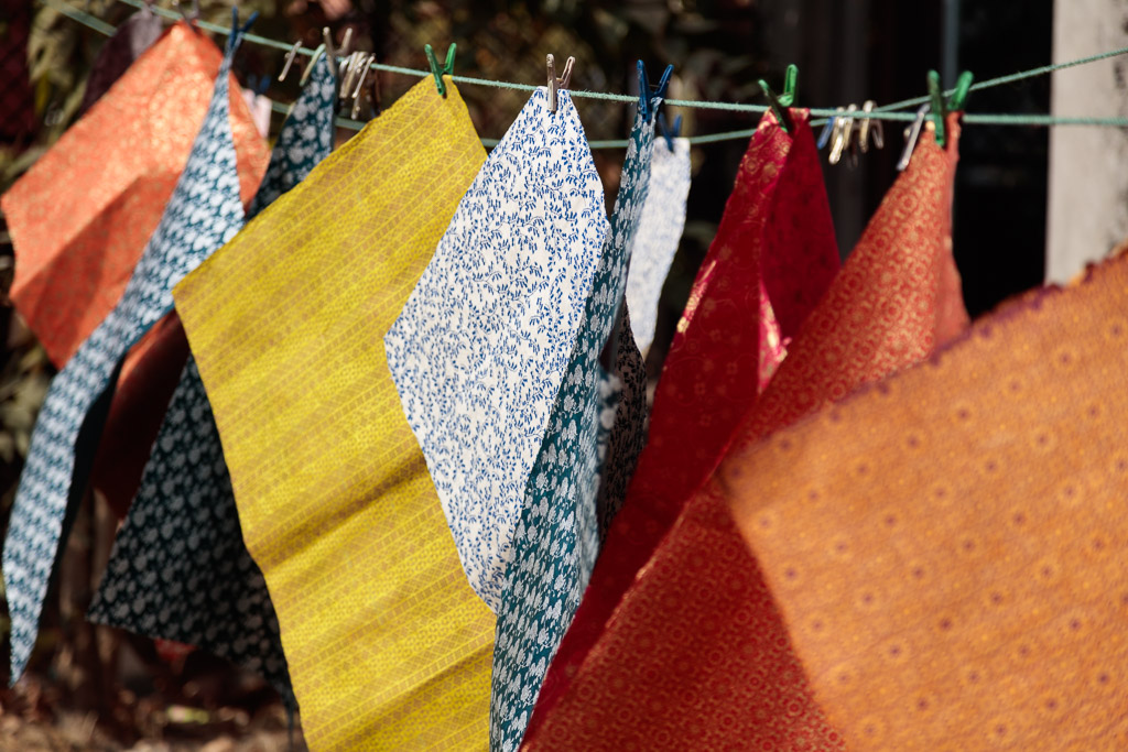Freshly printed Lokta papers hang on a line to dry.