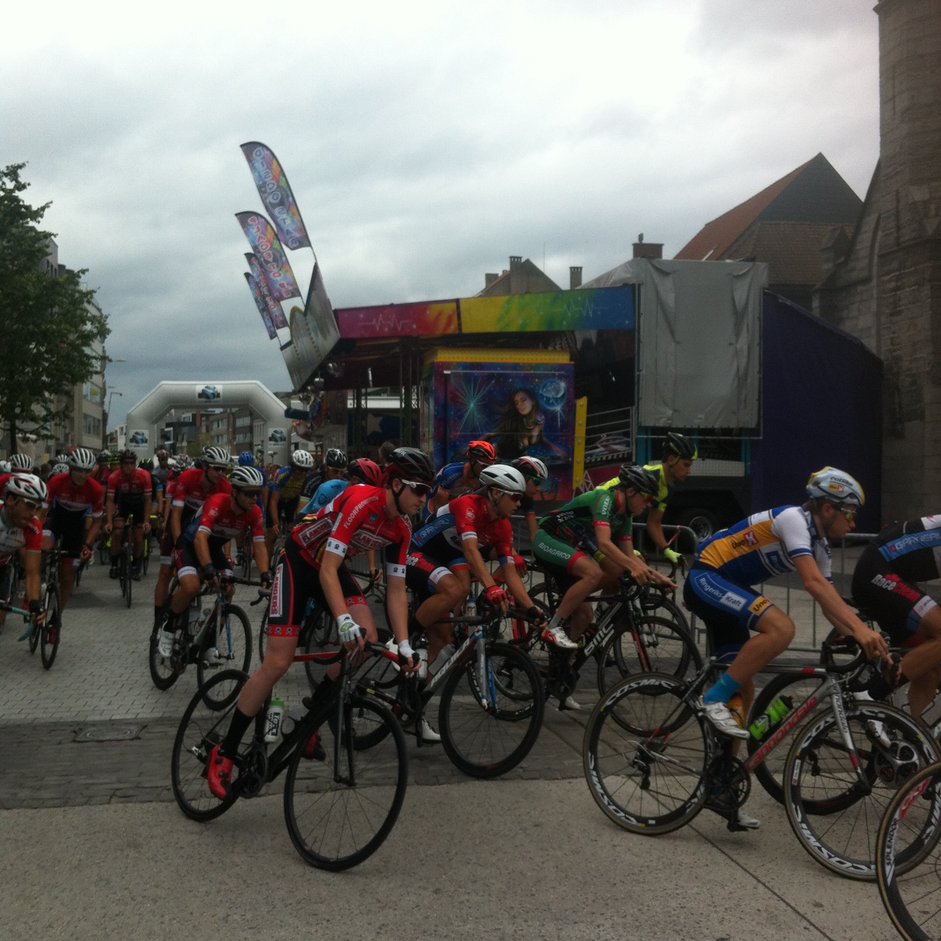 Conor (in red) at the Deinze start, passing the main kermis entertainment tent (beside the Church !)